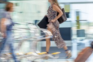 A woman frantically running through the airport chaos in need of silence to relax.