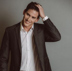 A professional photo of Creative Director Andy Felice. He is looking to his right, running his left hand through his hair while smiling. The owner and operator of Felice Marketing